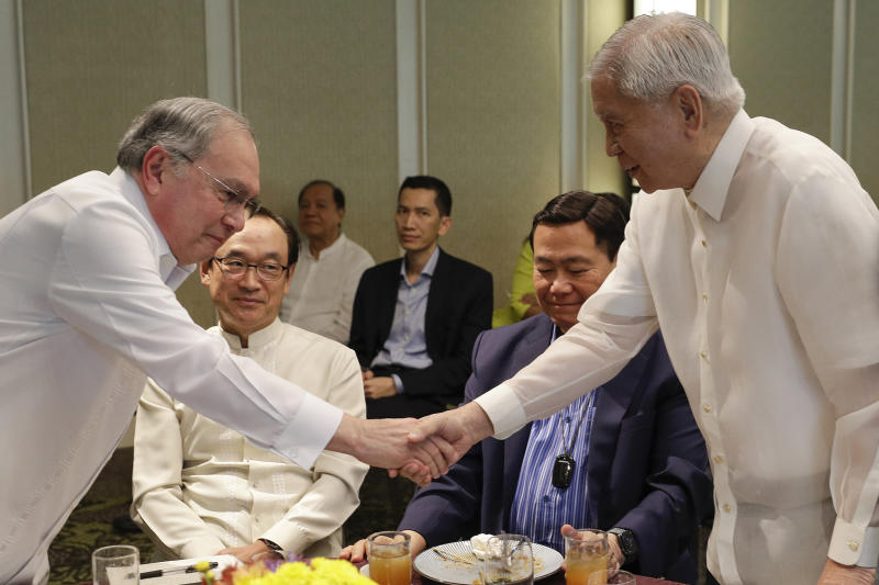 Former Philippines Foreign Secretary Albert del Rosario, right, shakes hands with Jose Manuel Romualdez, ambassador of the Philippines to the U.S., during a forum in Makati, metropolitan Manila, Philippines on Friday, Feb. 28, 2020. Rosario warned Friday the president's move to end a key U.S. security pact will undermine the ability of American forces to help the country deal with major disasters, modernize its military and deter aggression in the disputed South China Sea. (AP Photo/Aaron Favila)