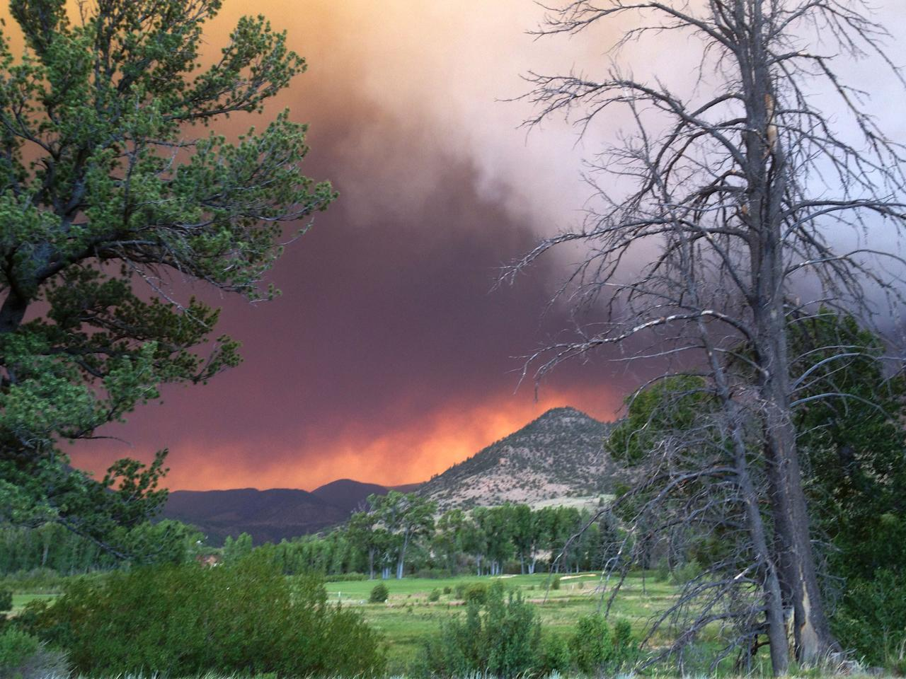 In this Thursday, June 20, 2013 photo provided by the U.S. Forest Service, wildfires fires approach the town of South Fork, Colo. The town of about 400 people was evacuated Friday morning, June 21, 2013. (AP Photo/U.S. Forest Service, Penny Bertram)