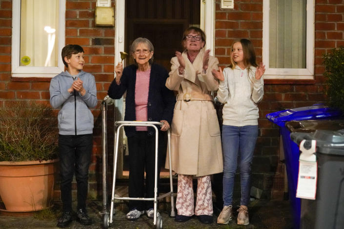 """MANCHESTER,  - MARCH 26: Barbara Leigh, aged 93, (second left) rings a bell for the NHS, with her family who are all staying together throughout the lockdown, from their front garden across the road from Wythenshawe Hospital on March 26, 2020 in Manchester, United Kingdom. The """"Clap For Our Carers"""" campaign has been encouraging people across the U.K to take part in the nationwide round of applause from their windows, doors, balconies and gardens at 8pm to show their appreciation for the efforts of the NHS as they tackle the coronavirus (COVID-19). The coronavirus pandemic has spread to many countries across the world, claiming over 20,000 lives and infecting hundreds of thousands more. (Photo by Christopher Furlong/Getty Images)"""