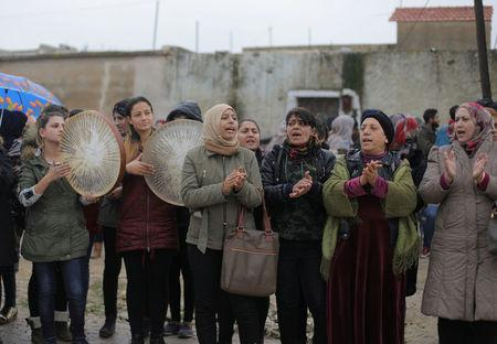 Women chant slogans during a protest near the Syrian-Turkish border in Ras al-Ayn town