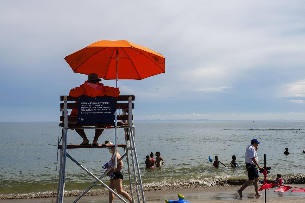 A lifeguard watches as beachgoers enjoy the water at Coney Island Beach on the first day swimming is allowed at New York City beaches on July 1, 2020.