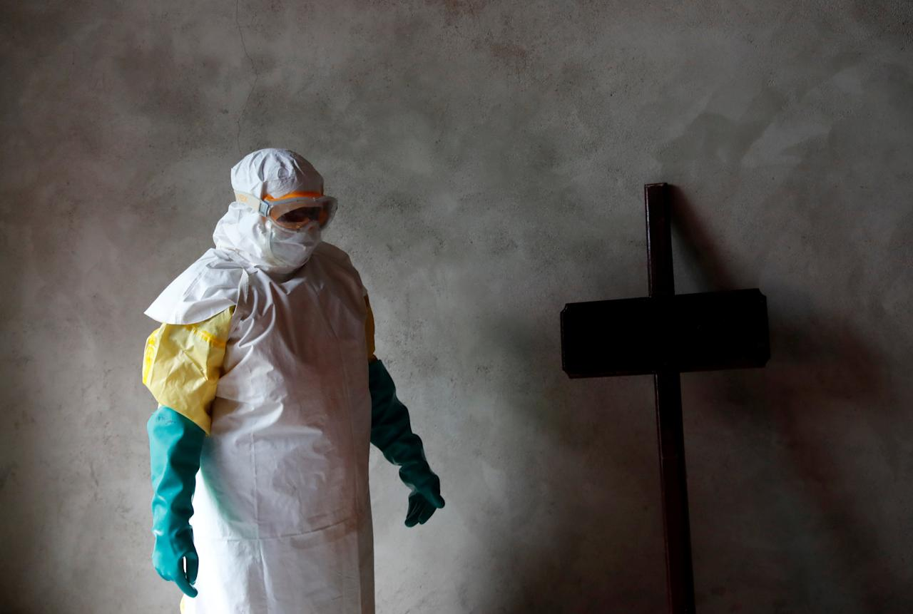 REFILE - REMOVING NAME A healthcare worker stands next to a cross during a funeral of a person who is suspected of dying of Ebola in Beni, North Kivu Province of Democratic Republic of Congo, December 9, 2018.   REUTERS/Goran Tomasevic