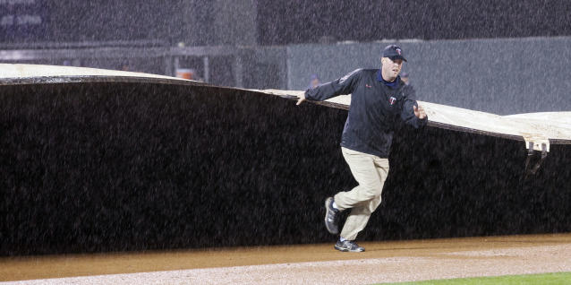 A member of the Target Field grounds crew helps pull the tarp onto the field during a fourth inning rain delay of a baseball game between the Minnesota Twins and the Tampa Bay Rays, Saturday, Sept. 14, 2013, in Minneapolis. (AP Photo/Paul Battaglia)