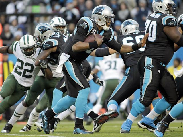 Carolina Panthers' Cam Newton, center, rushes for a first down against the New York Jets during the first half of an NFL football game in Charlotte, N.C., Sunday, Dec. 15, 2013. (AP Photo/Bob Leverone)