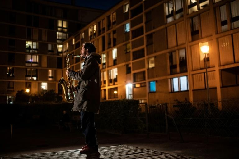 A musician plays the saxophone in a Paris neighbourhood on the 10th day of a strict lockdown in France (AFP Photo/Martin BUREAU)