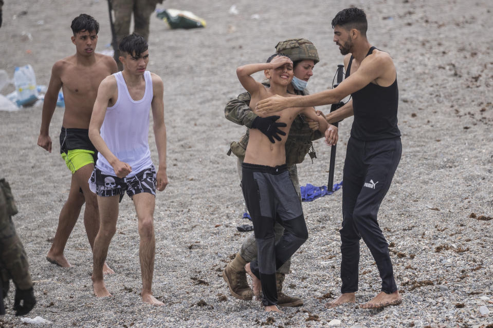 A boy is assisted by a soldier of the Spanish Army near the border of Morocco and Spain, at the Spanish enclave of Ceuta, on Tuesday, May 18, 2021. Ceuta, a Spanish city of 85,000 in northern Africa, faces a humanitarian crisis after thousands of Moroccans took advantage of relaxed border control in their country to swim or paddle in inflatable boats into European soil. (AP Photo/Bernat Armangue)