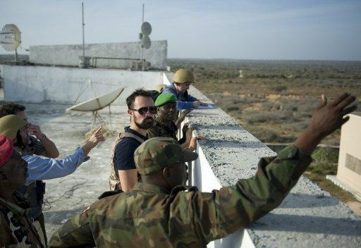 Russia's Evgeny Lebedev (C), 31, gets a brief from an African Union Troops Commander during a tour of a frontline area near the Mogadishu university in Somalia's war-shattered capital. Lebedev is the son of Russian oligarch Alexander Lebedev and a British press baron