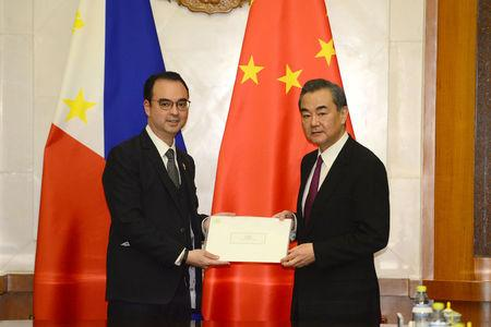 Philippine Foreign Affairs Secretary Alan Peter Cayetano, left, passes on a hand-written letter from President Rodrigo Duterte to Chinese President Xi Jinping during a meeting with Chinese Foreign Minster and State Counselor Wang Yi, right, at the Diaoyutai State Guesthouse in Beijing, China March 21, 2018. Parker Song/Pool via REUTERS