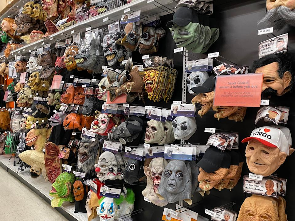 Various masks hanging in a party city store