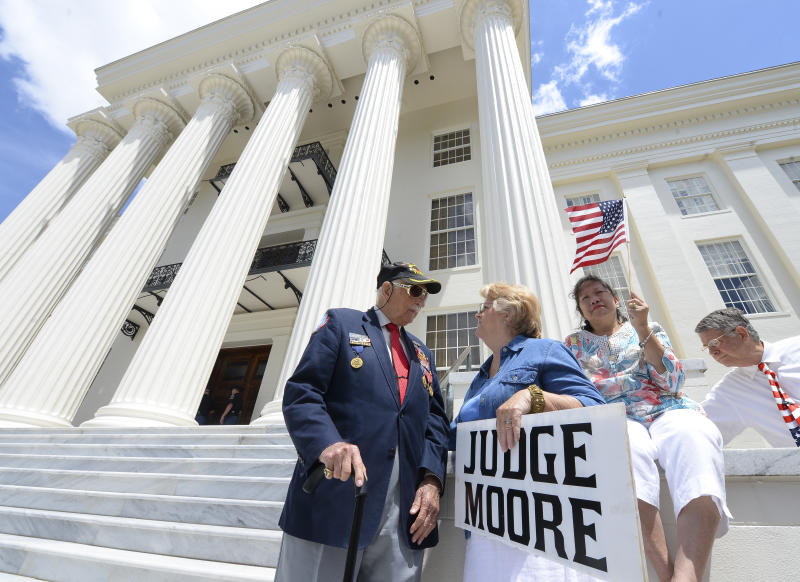 Supporters of suspended Alabama Chief Justice Roy Moore gather to listen to him announce his plan to run for U.S. Senate at a news conference Wednesday, April 26, 2017, on the steps of the Capitol in Montgomery, Ala. The fiery Republican jurist, who was suspended from the bench on accusations that he urged defiance of the landmark U.S. Supreme Court decision allowing gays and lesbians to marry, is running for the U.S. Senate seat previously held by Attorney General Jeff Sessions. (Julie Bennett/AL.com via AP)