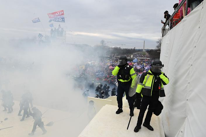 Police gather near tear gas as supporters of US President Donald Trump protest outside the US Capitol on January 6, 2021, in Washington, DC. - Demonstrators breeched security and entered the Capitol as Congress debated the a 2020 presidential election Electoral Vote Certification. (Photo by ROBERTO SCHMIDT / AFP) (Photo by ROBERTO SCHMIDT/AFP via Getty Images)