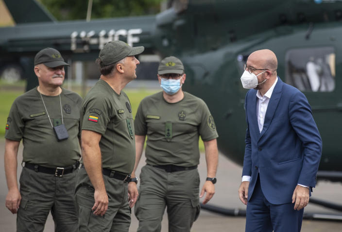 European Council President Charles Michel, right, speaks with members of the Lithuania State Border Guard as he arrives at the Border Guard School near Lithuanian-Belarusian border, near the village Medininkai, some 25 km (24 miles) east of the capital Vilnius, Lithuania, Tuesday, July 6, 2021. (AP Photo/Mindaugas Kulbis)