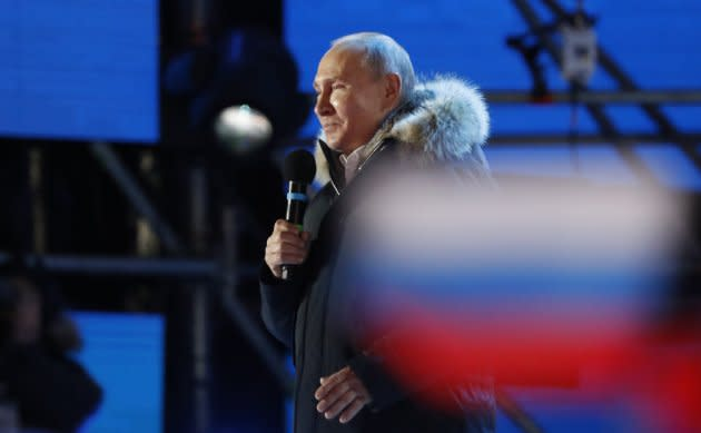Russian President Vladimir Putin delivers a speech during a rally and concert marking the fourth anniversary of Russia's annexation of the Crimea region, at Manezhnaya Square in central Moscow on March 18, 2018.