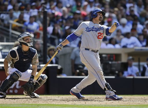 Los Angeles Dodgers' Adrian Gonzalez and San Diego Padres catcher Nick Hundley, left, watch the flight of Gonzalez' ninth-inning home run gaving the Dodgers the lead in a baseball game eventually won by the Dodgers 3-1 in San Diego, Sunday, June 23, 2013. (AP Photo/Lenny Ignelzi)