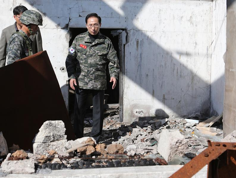 South Korean President Lee Myung-bak, center, visits a demolished building on Yeonpyeong Island near the Yellow Sea border with North Korea, South Korea, Thursday, Oct. 18, 2012. The island was bombarded in North Korea's shelling attack in November 2010, leaving two South Korean Marines and two civilians dead.(AP Photo/Yonhap, Do Kwang-hwan) KOREA OUT