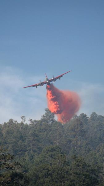In this June 1, 2012 photo provided by the U.S. Forest Service, a firefighting air tanker drops a load of fire retardant on the Gila National Forest blaze in New Mexico. Firefighters working in different parts of New Mexico are using similar tactics to corral two lightning-sparked wildfires. By Wednesday June 6, 2012, crews contained more than 20 percent of the massive Whitewater-Baldy fire in southwestern New Mexico. (AP Photo/U.S. Forest Service)