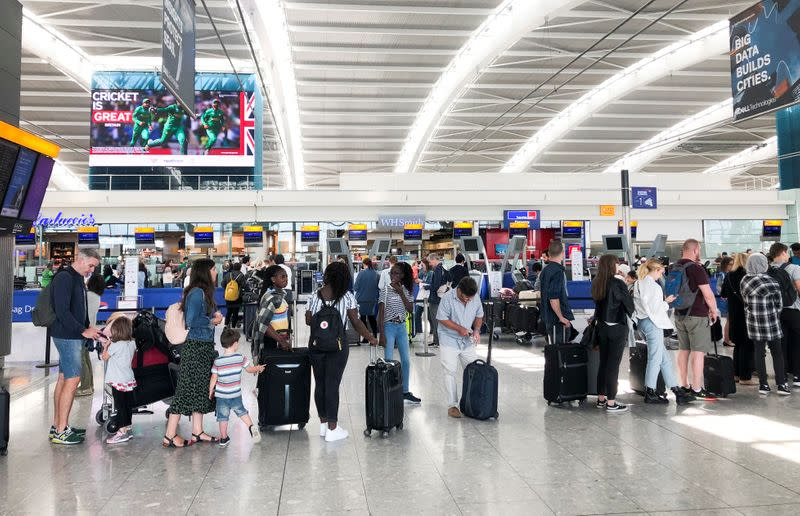 FILE PHOTO: People queue inside Terminal 5 at Heathrow Airport as IT problems caused delays in London