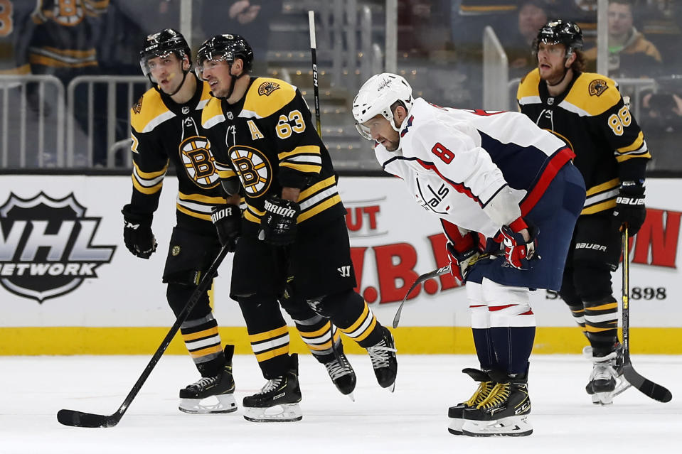 Washington Capitals' Alex Ovechkin bends over as Boston Bruins' Brad Marchand (63) leads teammates David Pastrnak (88) and Patrice Bergeron to the bench after a goal during the first period of an NHL hockey game Monday, Dec. 23, 2019, in Boston. (AP Photo/Winslow Townson)