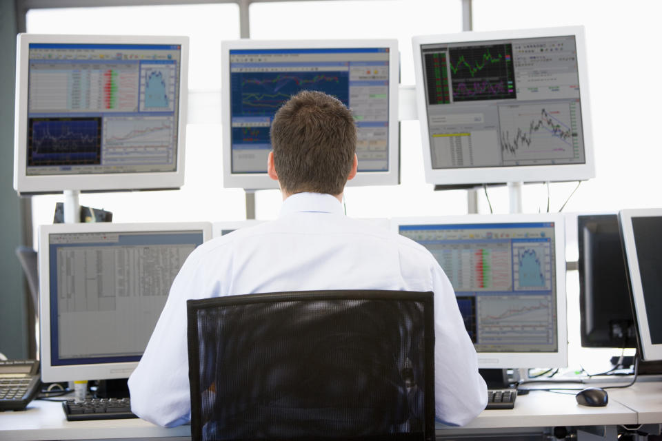 Stock Trader Looking At Multiple Monitors Working In Office