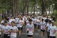 """Supporters of the anti-military Future Forward Party participate in a run dubbed as """"Run Against Dictatorship"""" at a park in Bangkok, Thailand, Sunday, Jan. 12, 2020. About 6000 runners participated in a 3 kilometer run to demonstrate against the government led by former army general Prayuth Chan-ocha. (AP Photo/Gemunu Amarasinghe)"""