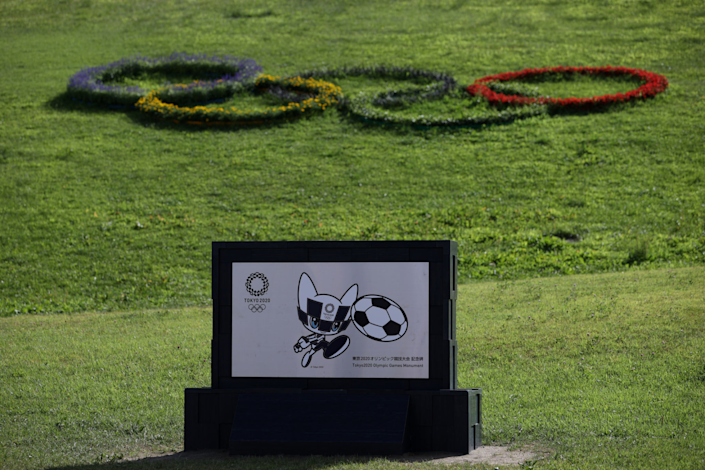 A black-and-white Olympic mascot kicks a soccer ball on a sign at the Tokyo Olympics.