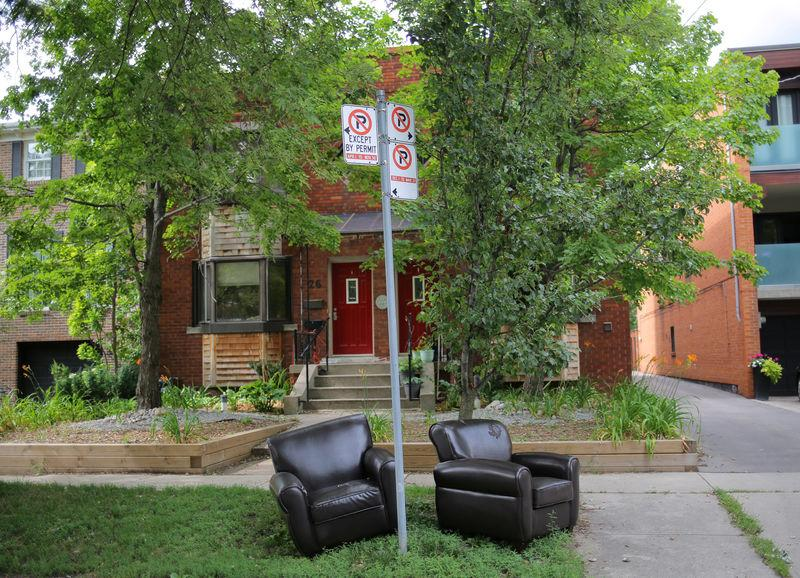 A pair of lounge chairs lie on a curb In a residential street in midtown Toronto