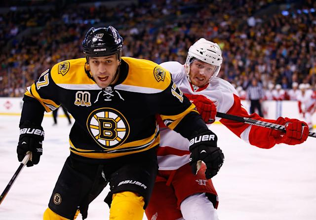 BOSTON, MA - APRIL 20: Milan Lucic #17 of the Boston Bruins and Gustav Nyquist #14 of the Detroit Red Wings skate to the puck in the corner in the second period during the game at TD Garden on April 20, 2014 in Boston, Massachusetts. (Photo by Jared Wickerham/Getty Images)