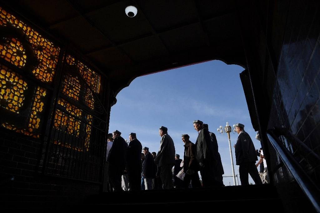 Uighur men walk make past a subway entrance after Eid al-Fitr prayers at the Id Kah mosque in Kashgar (AFP Photo/GREG BAKER)