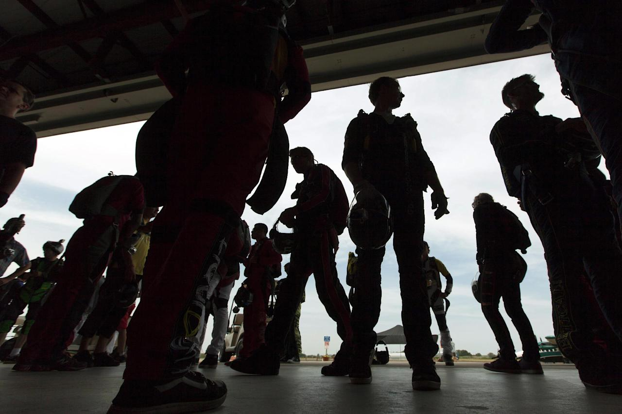 Skydivers are silhouetted at the entrance to a hangar as they prepare to board aircraft, Thursday, Aug. 2, 2012, in Ottawa, Ill. More than 140 skydivers reaching speeds in excess of 180 mph gathered in the skies over central Illinois to set a new world record in vertical flying. (AP Photo/Sitthixay Ditthavong)