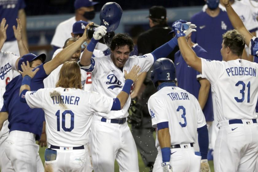 """The Dodgers' Cody Bellinger is welcomed by teammates after his walk-off home run during the ninth inning against the Colorado Rockies on Aug. 22. <span class=""""copyright"""">(Alex Gallardo / Associated Press)</span>"""
