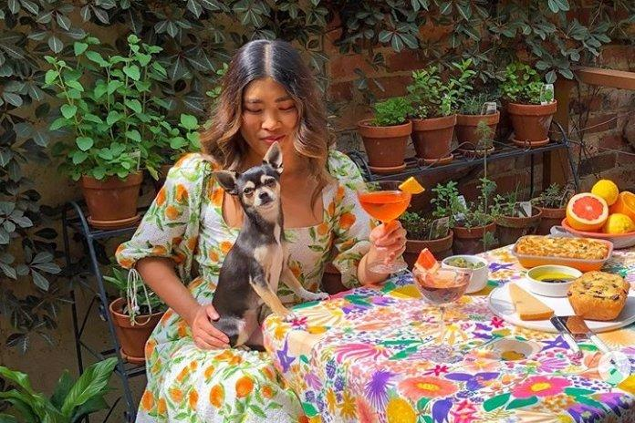 Melbourne woman Jessica Nguyen sits at a colourful table holding a dog.