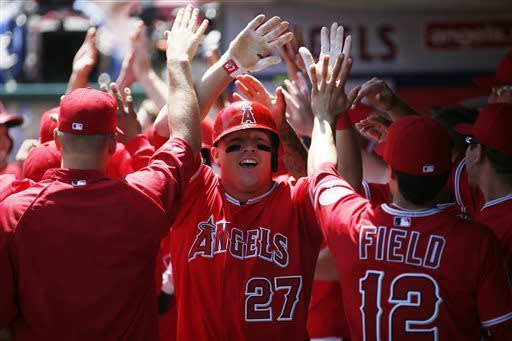 Los Angeles Angels' Mike Trout celebrates with teammates as he comes into the dugout after hitting a grand slam to also drive in Brendan Harris, Peter Bourjos and Luis Jimenez off Detroit Tigers starting pitcher Rick Porcello during the first inning of a baseball game on Saturday, April 20, 2013, in Anaheim, Calif. (AP Photo/Danny Moloshok)