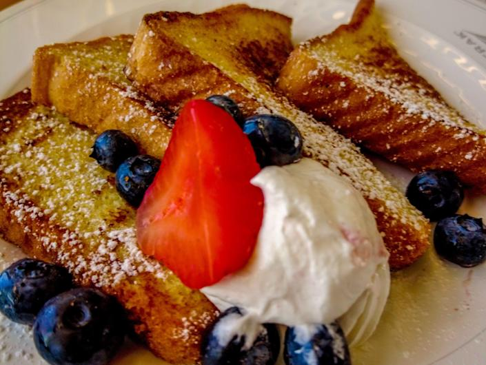 French toast with berries and cream on a white plate