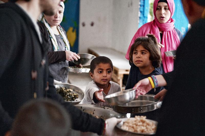 Refugees get meal cooked by chef Talal Rankoussi and volunteers at the 'Cafe Rits' in Ritsona refugee camp, some 80 km north of Athens (AFP Photo/Louisa GOULIAMAKI)