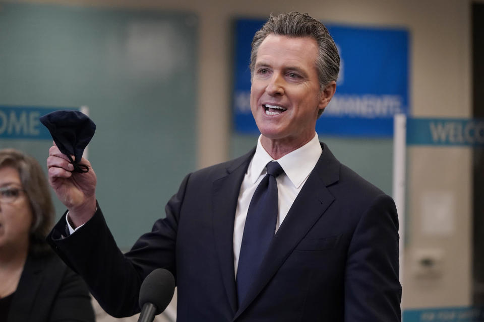 FILE — In this July 26, 2021 file photo Gov. Gavin Newsom holds a face mask while speaking at a news conference in Oakland, Calif. Conservative radio talk show host Larry Elder has emerged as the top contender for those who are looking to unseat Newsom in the Sept. 14th recall election. Elder, who is running to replace Newsom in the Sept. 14 recall election, says he would erase state vaccine and mask mandates, is critical of gun control, opposes the minimum wage and disputes the notion of systemic racism in America. (AP Photo/Jeff Chiu, File )