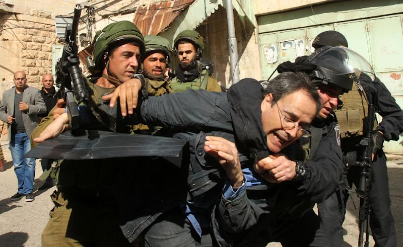 Israeli soldiers arrest an Israeli protester during clashes following a demonstration against Jewish settlements on February 20, 2016 in the West Bank city of Hebron (AFP Photo/Hazem Bader)
