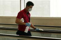 An airport worker sanitizes a walkway at Miami International Airport, Wednesday, Nov. 25, 2020, in Miami. (AP Photo/Lynne Sladky)