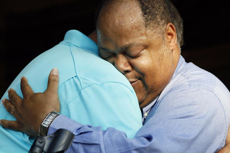 Rev. Stan Weatherford, pastor of the First Baptist Church of Crystal Springs, left, hugs Rev. Fitzgerald Lovett, pastor of New Zion United Methodist Church during a prayer rally in support of racial reconciliation Monday, July 30, 2012 following the actions of some congregants at the First Baptist Church which prevented a black couple from getting married there. (AP Photo/Rogelio V. Solis)