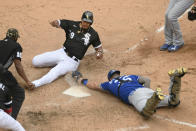 Chicago White Sox's Jose Abreu (79) slides safely into home plate while Kansas City Royals catcher Cam Gallagher attempts to apply the tag during the ninth inning of a baseball game Sunday, May 16, 2021, in Chicago. (AP Photo/Paul Beaty)