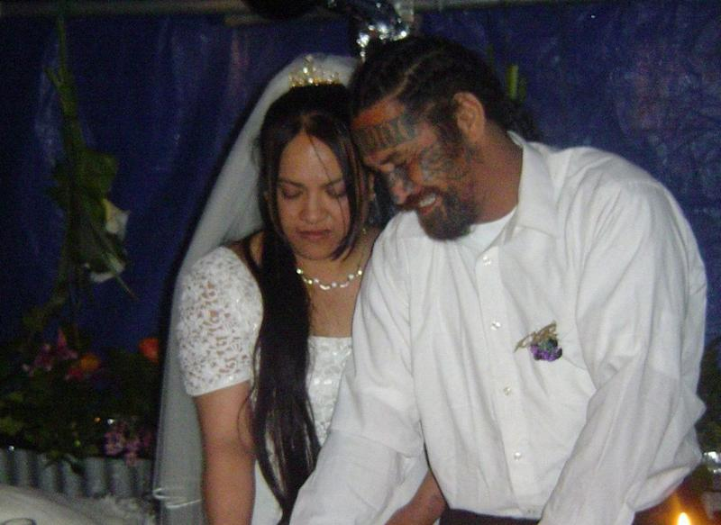 Berta Harrison-Ratima and her husband Malcolm Ratima. She's seen in a wedding dress and the couple are cutting a cake.