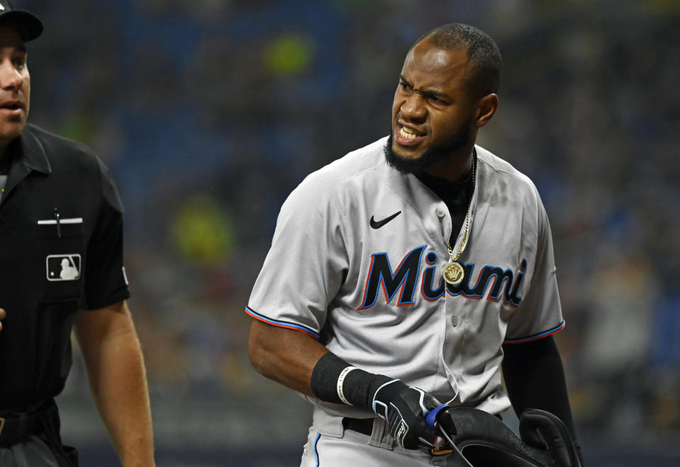Miami Marlins' Bryan De La Cruz, right, yells at home plate umpire John Libka when he was ejected after striking out during the first inning of a baseball game against the Tampa Bay Rays, Friday, Sept. 24, 2021, in St. Petersburg, Fla. (AP Photo/Steve Nesius)