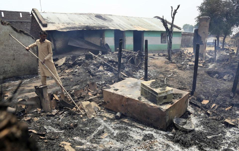 FILE - In this May 22, 2018, file photo, an Indian man inspects the damage after his home was gutted by firing allegedly from the Pakistan side of the border in Jora farm village, in Ranbir Singh Pura district of Jammu and Kashmir, India. Guns have fallen silent along the Line of Control, a de facto border that divides the Himalayan region of Kashmir between India and Pakistan after the rivals in February, 2021 reaffirmed their 2003 cease-fire accord. The somewhat surprising decision has prompted a thaw in the otherwise turbulent relations between the nuclear-armed South Asian neighbors, raising questions about how long the fragile peace will last. (AP Photo/Channi Anand, File)