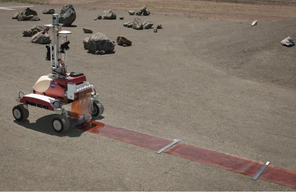 NASA's K10 rover at the Ames Research Center in Moffett Field,Calif., performs a surface survey with its cameras and laser system, and then deployed a simulated polymide antenna while being controlled by an astronaut in space during a June 201