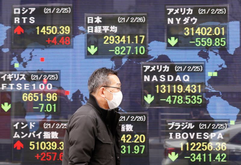 A man walks past a stock quotation board at a brokerage in Tokyo