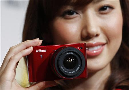 A model poses with Nikon Corp's new Nikon 1 J1 camera at its unveiling ceremony in Tokyo, in this September 21, 2011 file photo. REUTERS/Kim Kyung-Hoon/Files