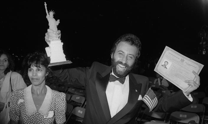 Yakov Smirnoff, smiling and in a dinner jacket, holds aloft a model of the Statue of Liberty and a certificate of his U.S. citizenship.