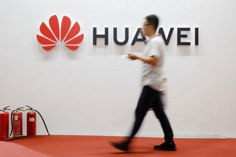 A man walks past a Huawei company logo at the International Consumer Electronics Expo in Beijing