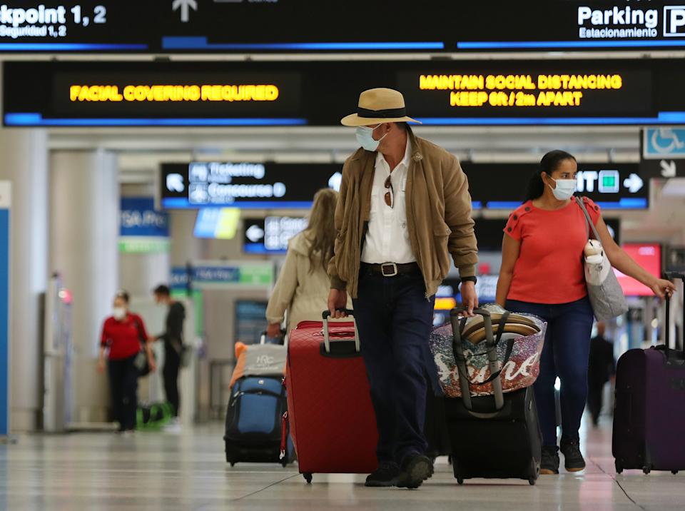 Travelers walk through Miami International Airport on February 01, 2021 in Miami, Florida. (Joe Raedle/Getty Images)