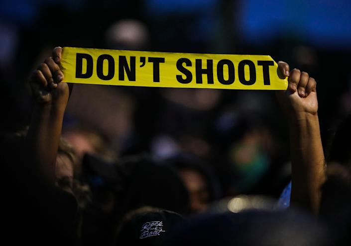 """<i>A protester holds up a piece of yellow plastic that reads, """"Don't shoot"""" while participating in a demonstration outside the Forest Hills MBTA Station in Boston on June 2.</i>"""