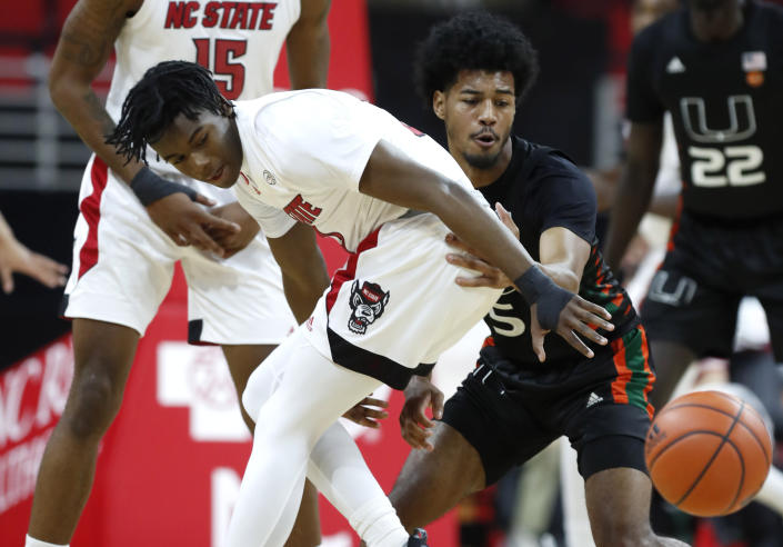 Miami's Harlond Beverly (5) steals the ball from North Carolina State's Cam Hayes (3) during the first half of an NCAA college basketball game at PNC Arena in Raleigh, N.C., Saturday, Jan. 9, 2021. (Ethan Hyman/The News & Observer via AP)